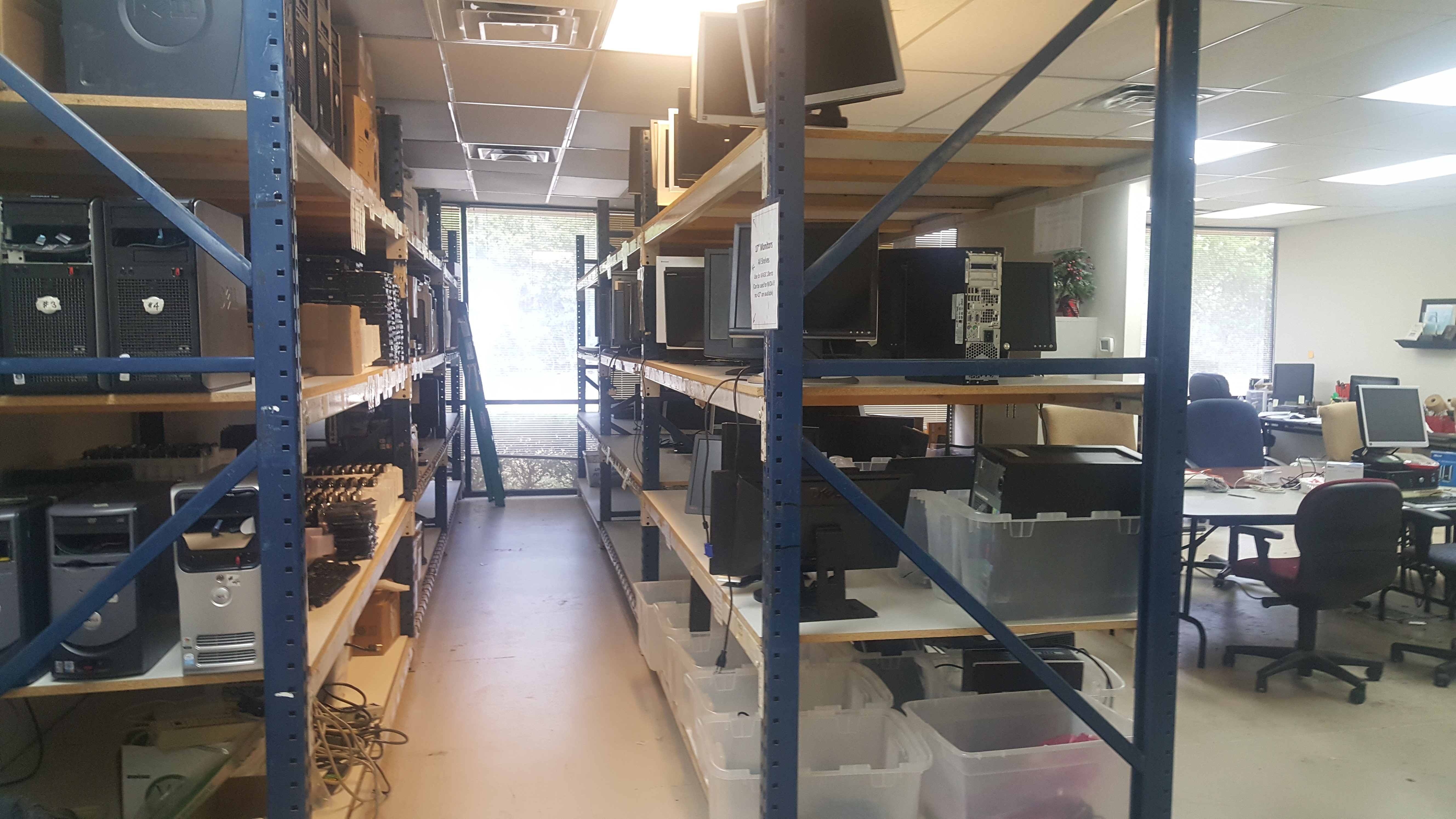 The storage shelves at our Refurbishing Center. On the right is our stock of monitors to ship out with desktops. On the left is our hard drive wiping station. We ensure drives are wiped to government standards before we use them in machines.