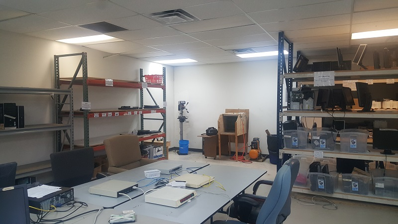 The storage shelves and work corner at the Refurbishing Center in Richardson. We use the drill press to destroy hard drives that cannot be used. Also visible is our air compressor, where we work to clean the machines before we ship them out.